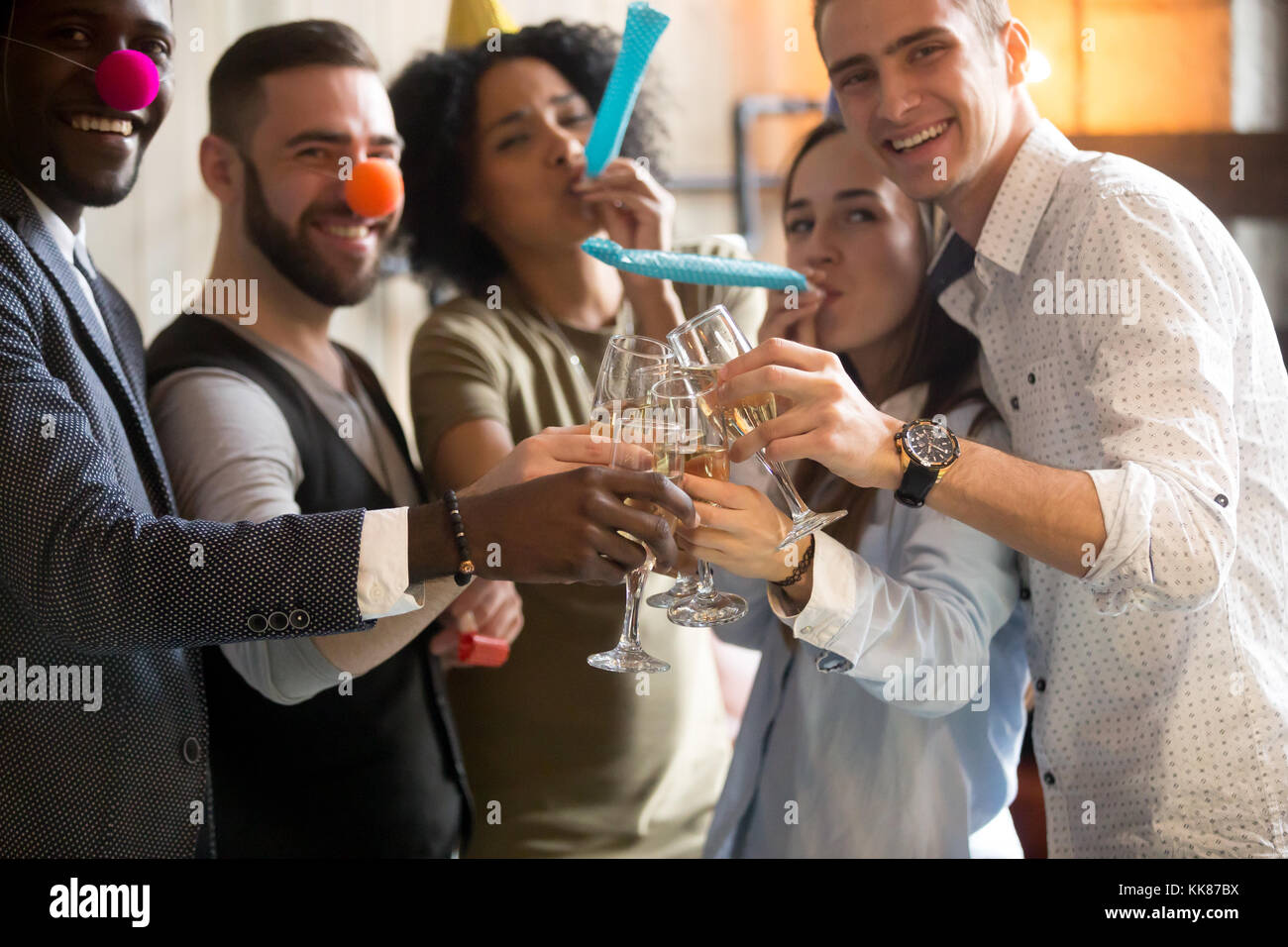 Multiracial young people clinking glasses blowing whistles celeb - Stock Image