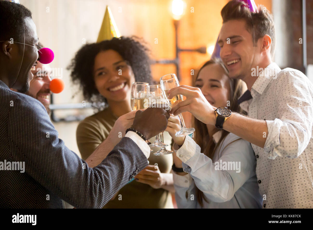 Happy black and white friends clinking glasses celebrating party - Stock Image