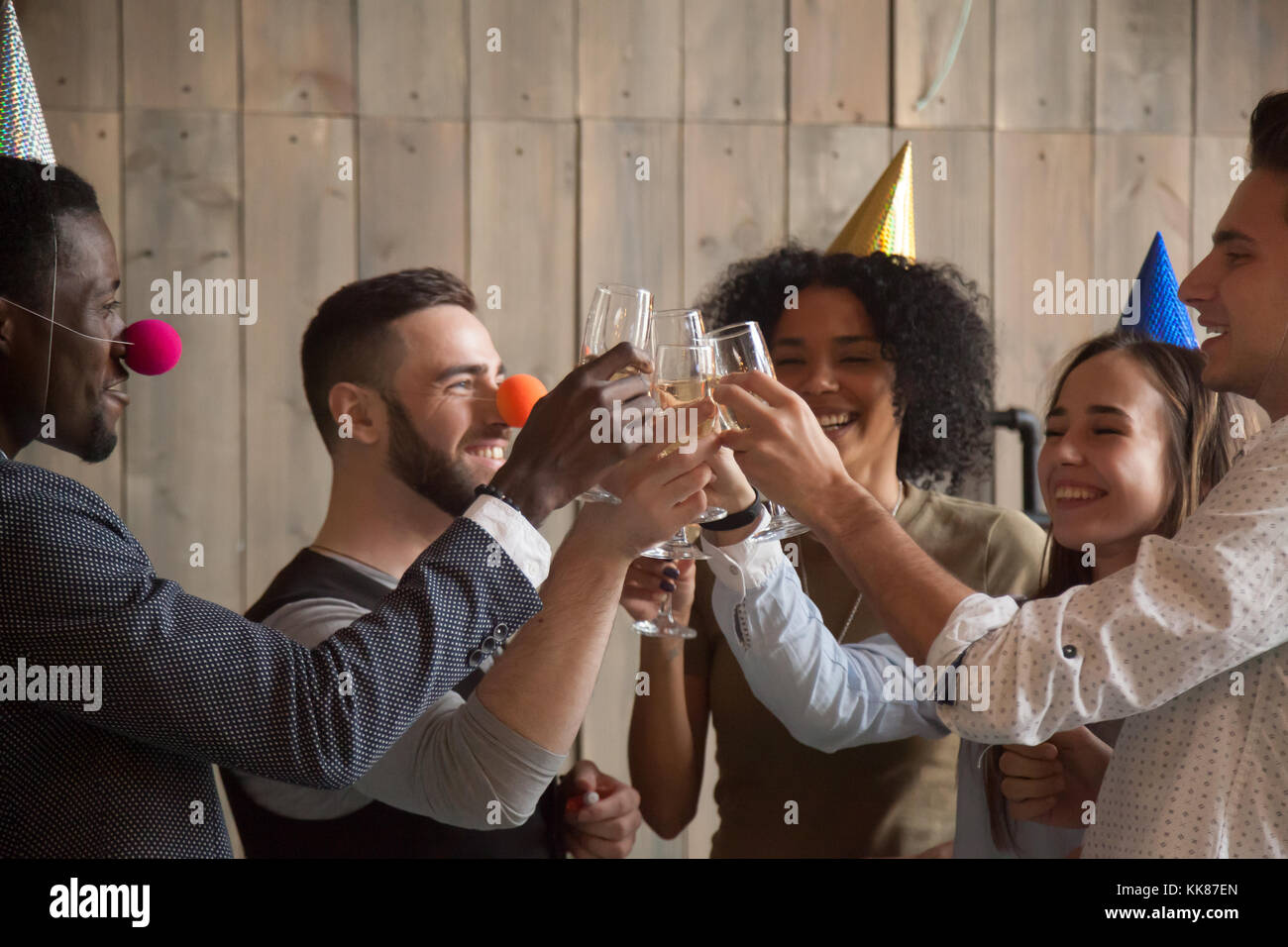 African and caucasian young friends clinking glasses celebrating - Stock Image