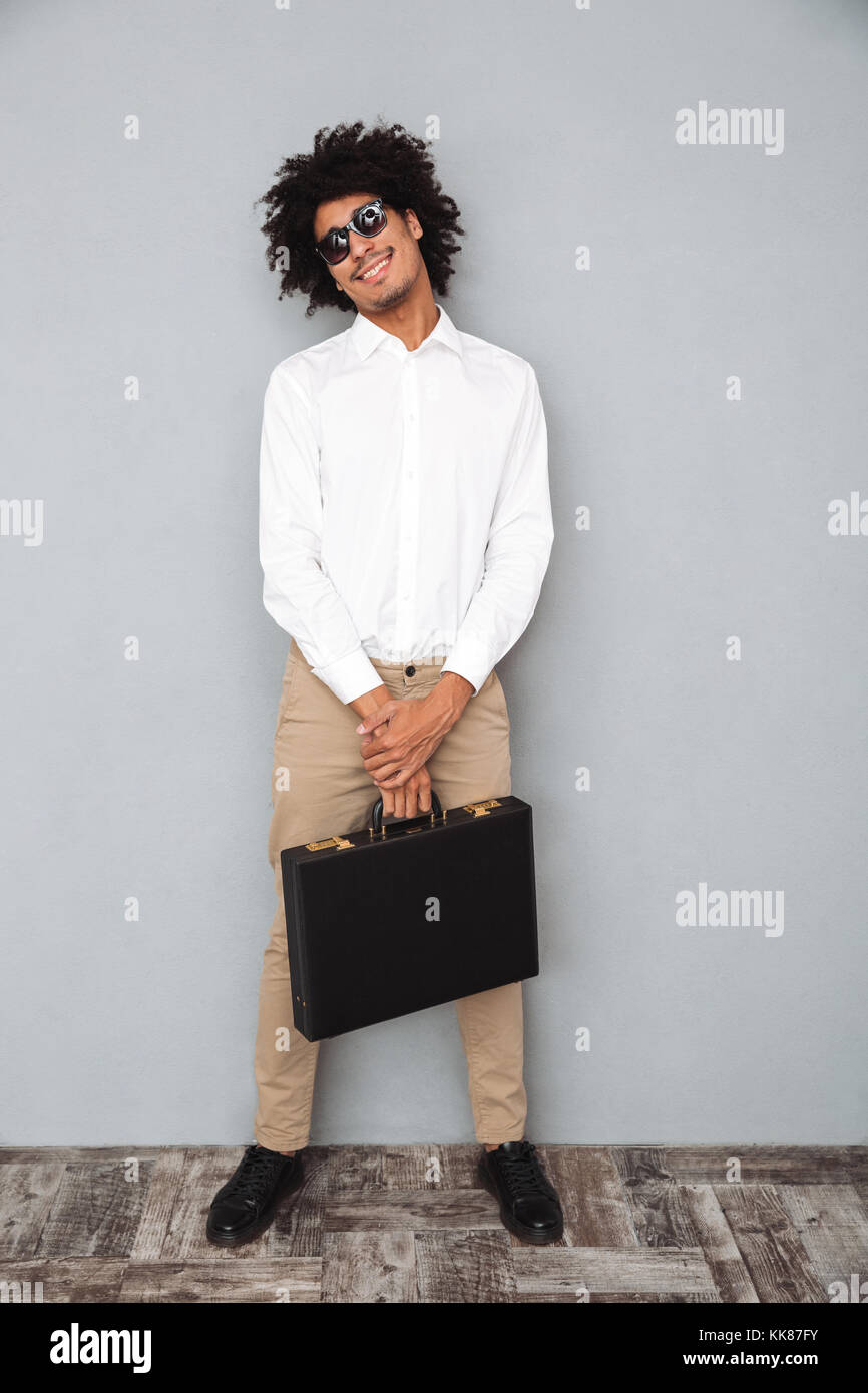 Full length portrait of a successful smiling african man in white shirt holding briefcase while standing and looking - Stock Image