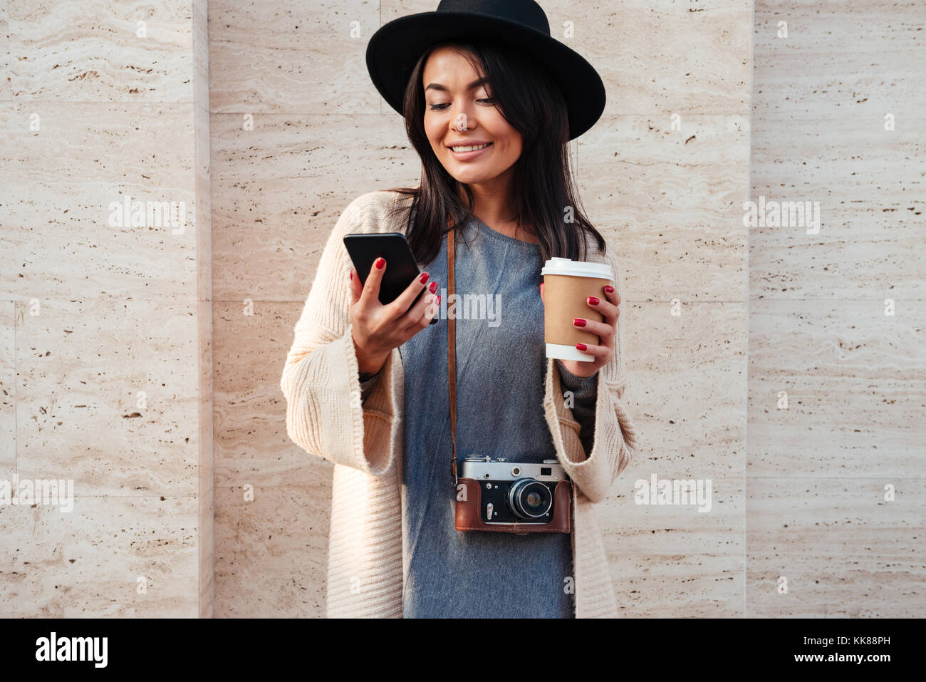 Young stylish asian woman in black hat using mobile phone and holding  coffee cup while standing on street 7da824fea0c
