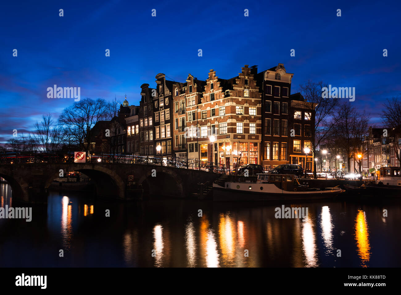 Typical Amsterdam canal houses in historic architecture along the canals a bridge over the water, illuminated at - Stock Image