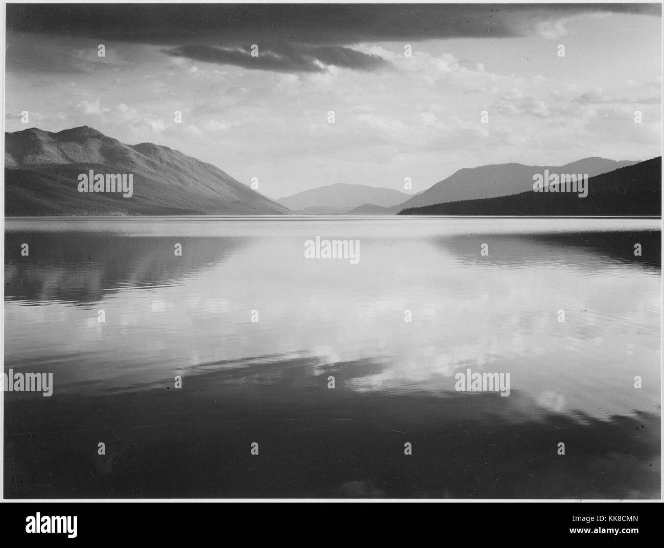 A black and white photograph of the flat surface of McDonald Lake in Glacier National Park, the background of the - Stock Image