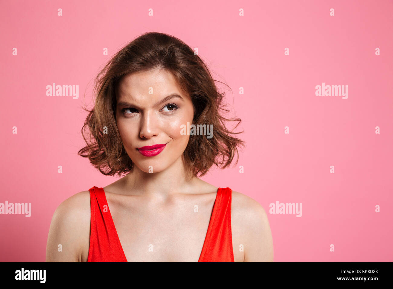 Close up portrait of a tricky pretty woman wearing bright make up looking away at copy space isolated over pink - Stock Image