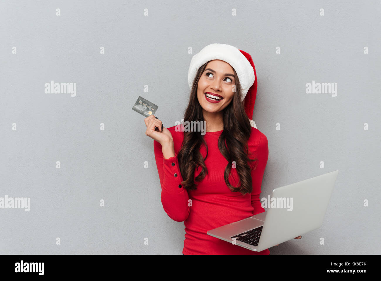 Charming brunette woman in Santa's hat and red blouse holding credit card and laptop computer, looking aside - Stock Image