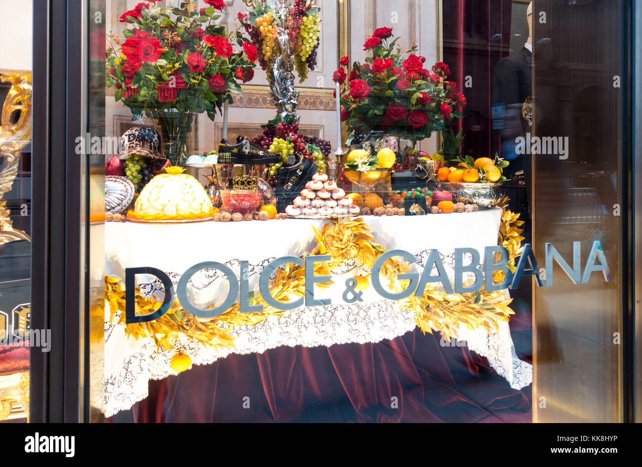 2017 Dolce & Gabbana Holiday window display showing a table of food - Stock Image