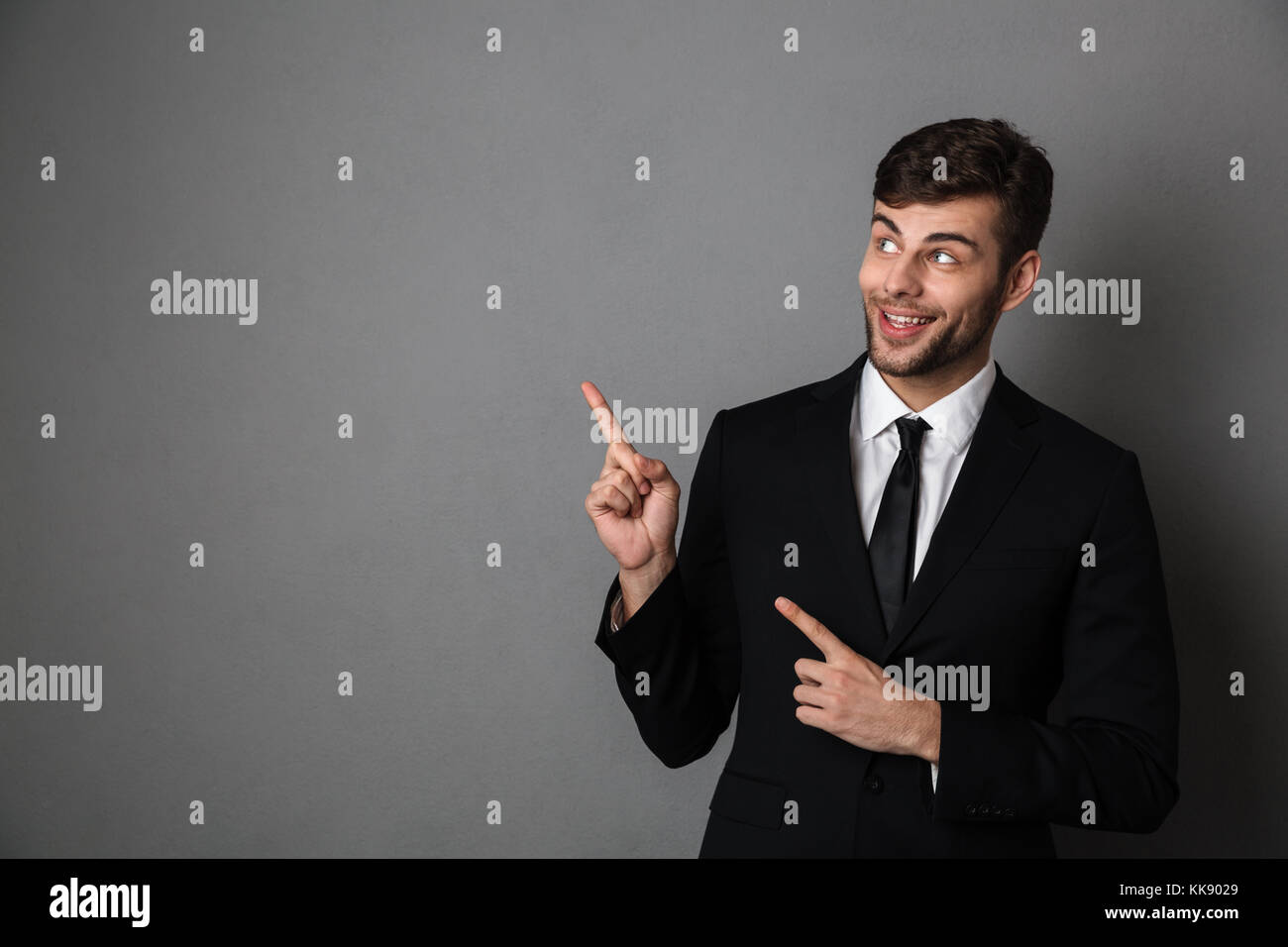 Close-up photo of handsome bearded man in black suit poiting with rwo fingers, looking aside, isolated on gray background - Stock Image