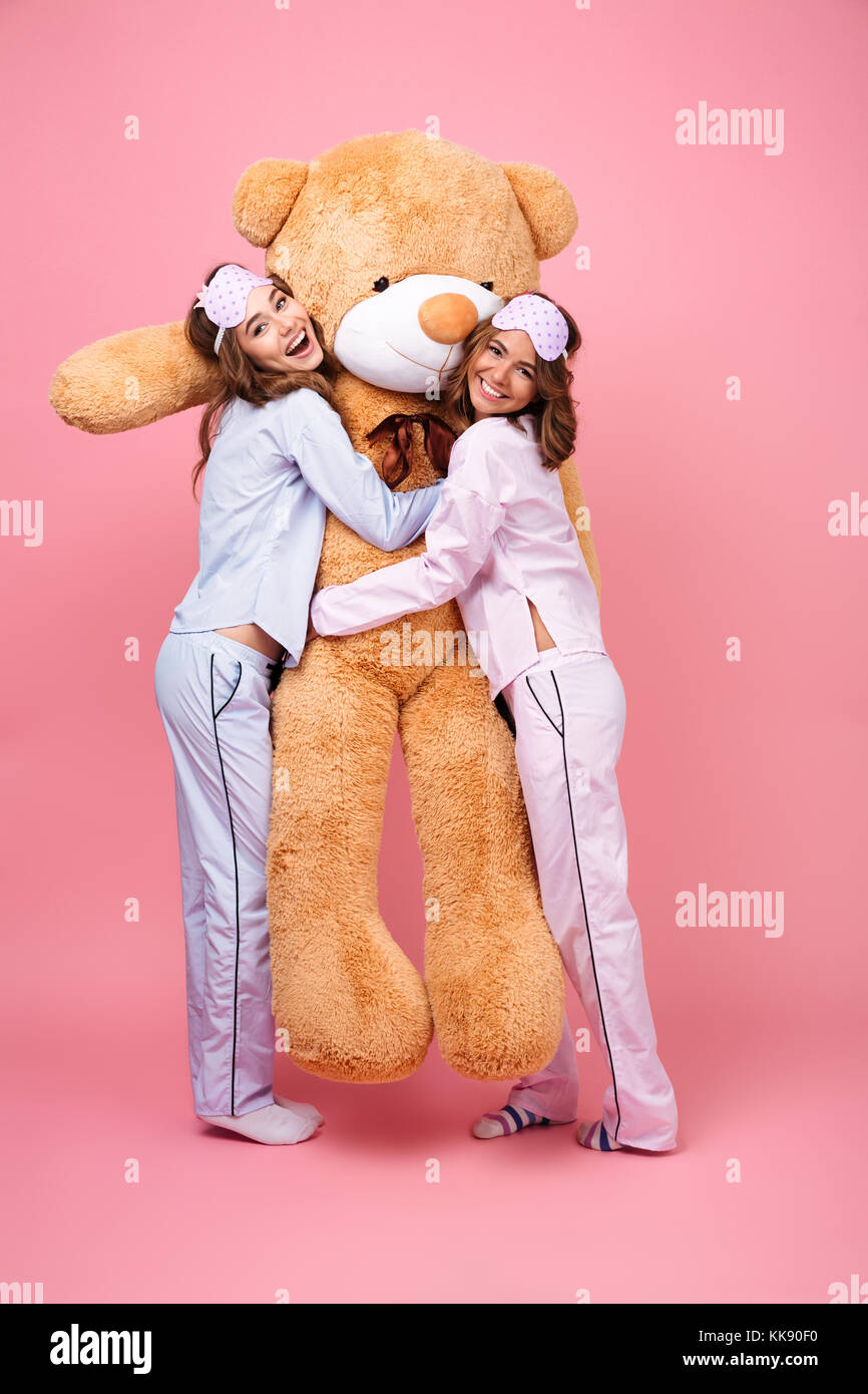 Picture of two cheerful friends women in pajamas isolated over pink  background hug big teddy toy fc86eda98