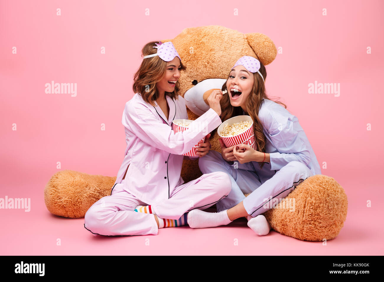 Two cheerful pretty girls dressed in pajamas sitting with a big teddy bear  and eating popcorn isolated over pink background 19b0c46d9
