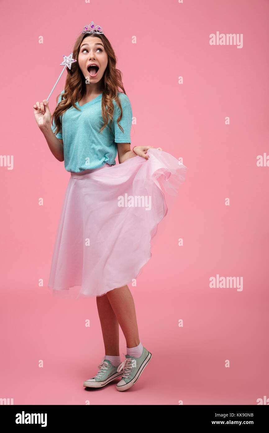 Full length portrait of a young pretty girl dressed in fairy costume holding a magic wand while standing and looking away isolated over pink backgroun  sc 1 st  Alamy & Full length portrait of a young pretty girl dressed in fairy costume ...
