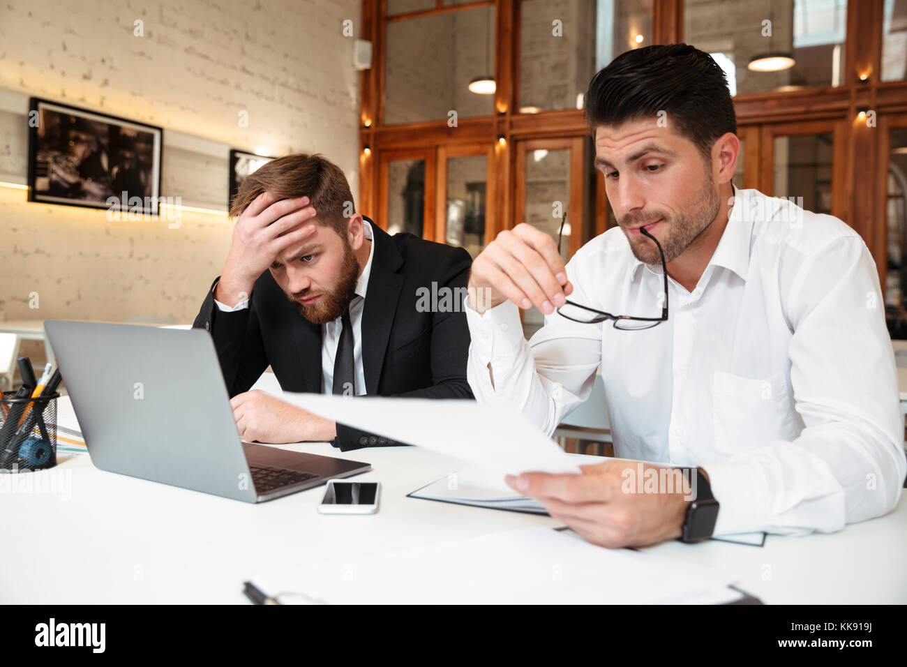 Two handsome bisinessman in formal wear working together while trying to solve problem in office - Stock Image