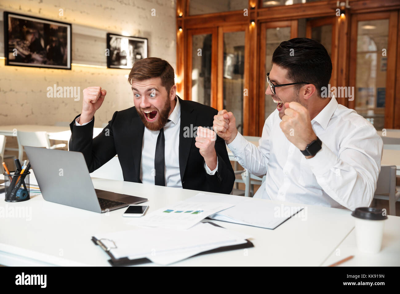 Two successful employees looking at a computer monitor on the table while expressing their achievement in the office - Stock Image