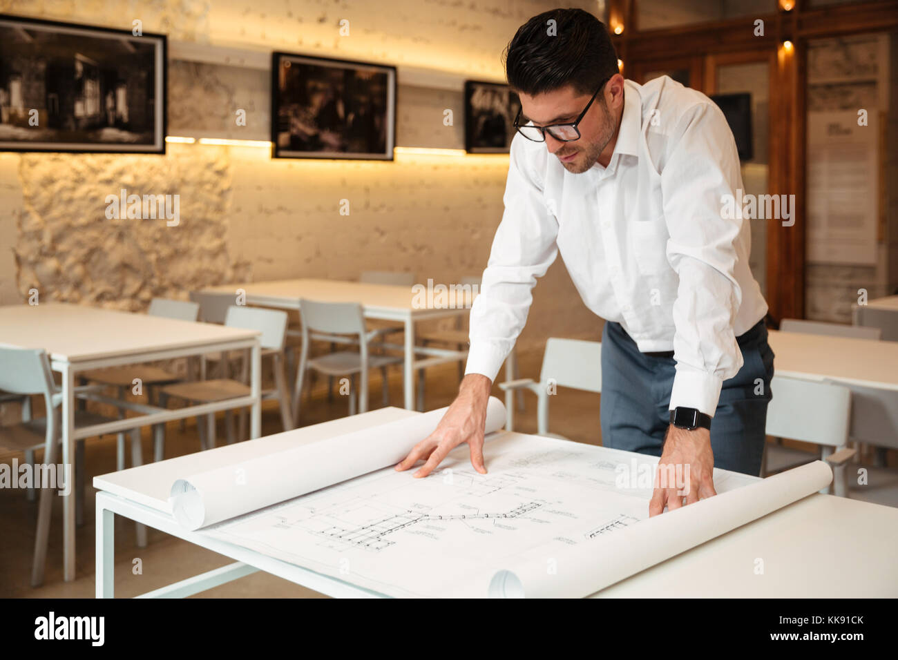 Portrait of a confident young businessman working with graphs and schematics indoors - Stock Image