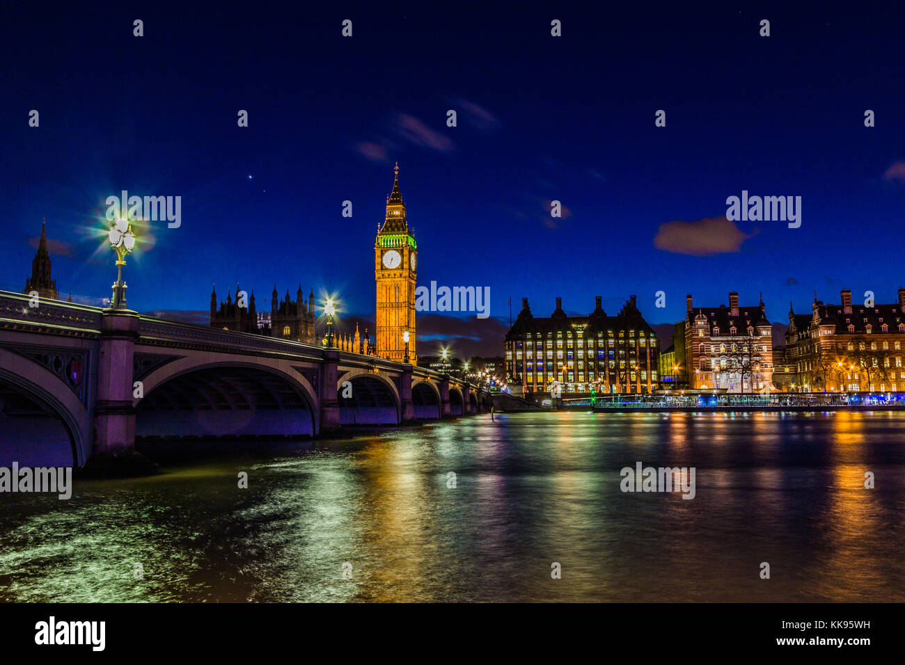 Famous landmark, Big Ben clock tower at night taken from the South side of the Thames River in central London. - Stock Image