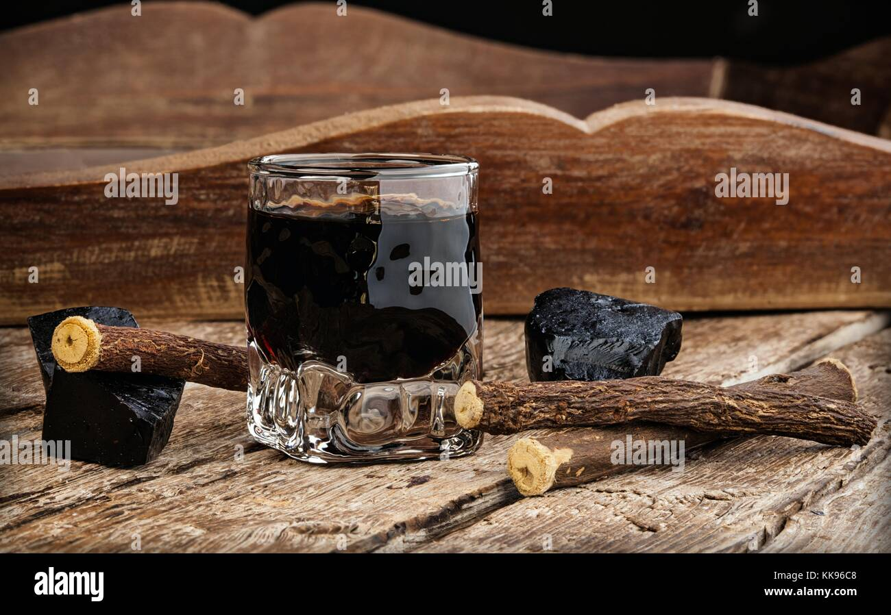 Licorice liqueur with pure blocks and roots - Stock Image