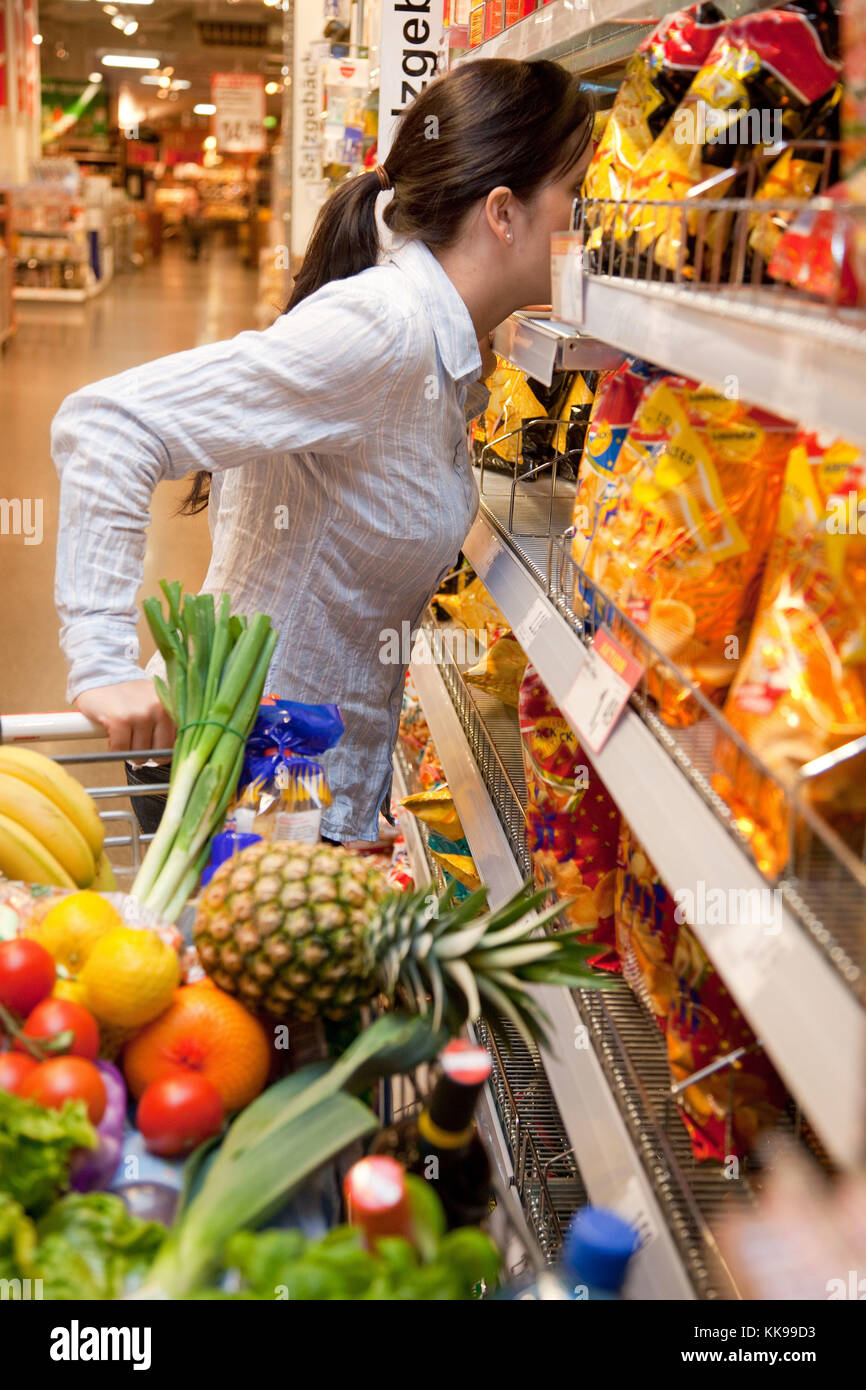 Young woman with shopping cart in the supermarket when shopping   usage worldwide - Stock Image