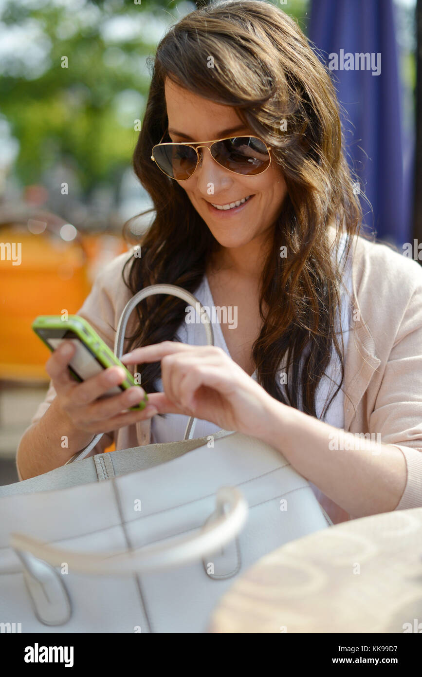 A woman with her mobile is doing some shopping in the city. (model released)   usage worldwide - Stock Image