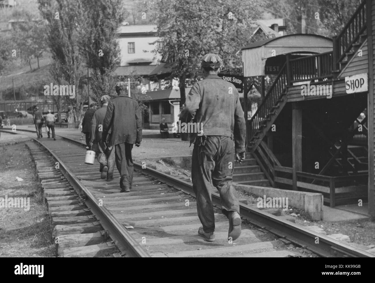Black and white photograph of a group of coal miners walking on train tracks after work omar west virginia september 1938