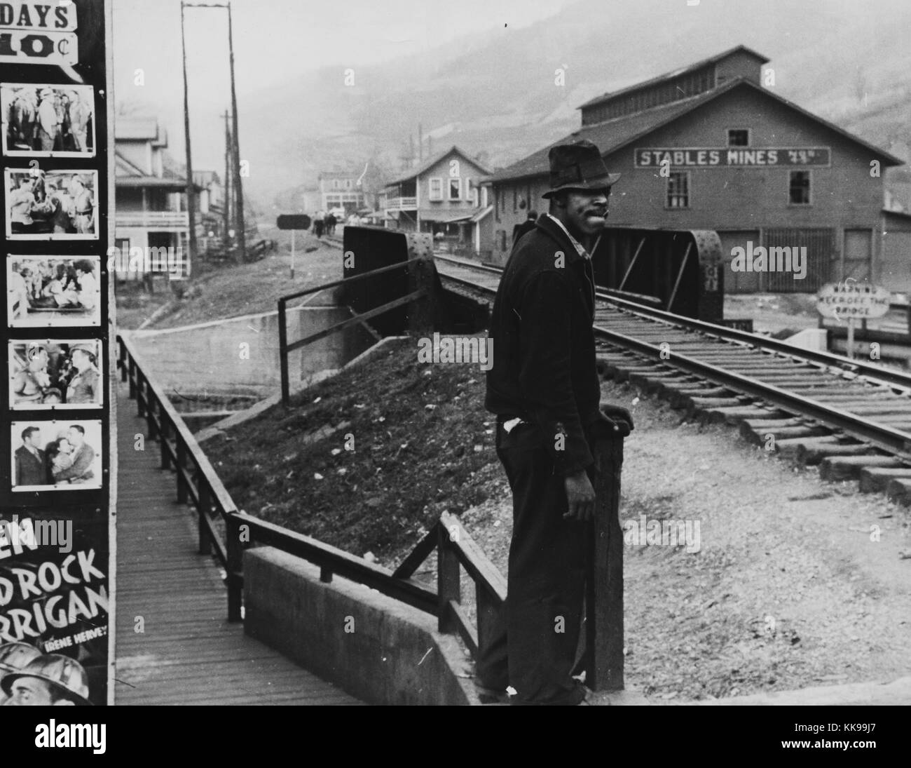 Black and white photograph of an african american man wearing a jacket and hat standing at a train stop buildings can be seen in the background omar