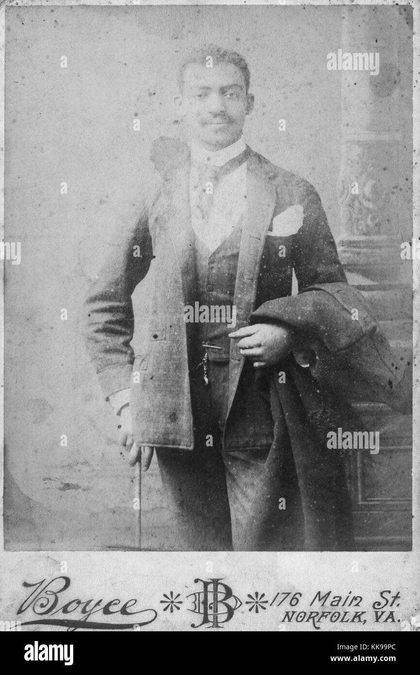 Sepia studio photograph of an African-American man, three-quarter length, wearing a suit, coat draped over his arm, - Stock Image