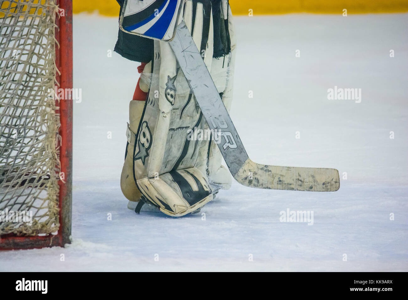 Closeup image of hockey goalkeeper's legs and feet in red and black uniform skating on ice - Stock Image