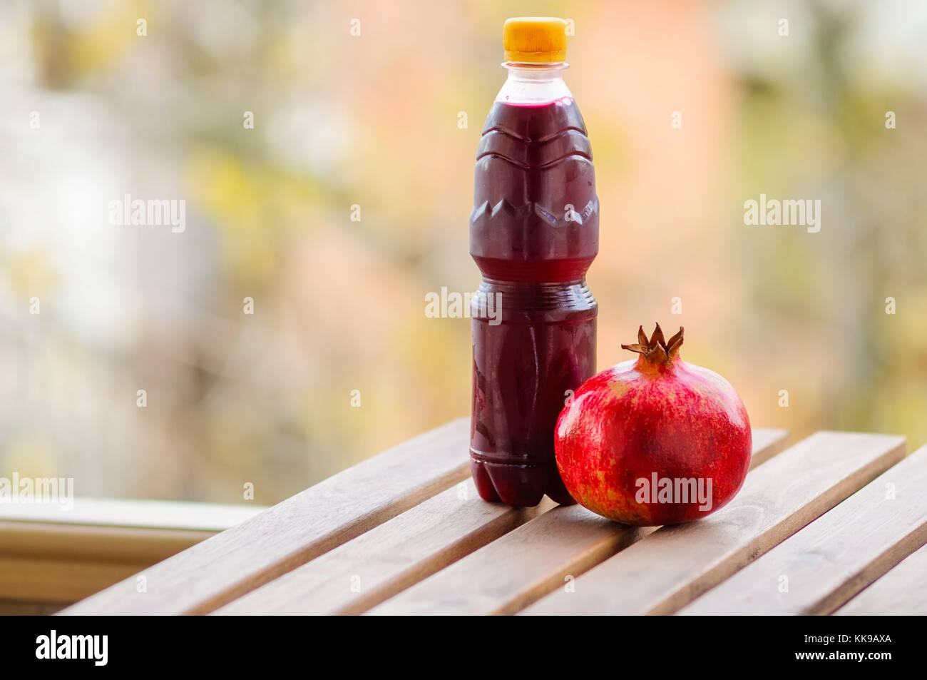 Pomegranate and bottle of juice on wooden table - Stock Image