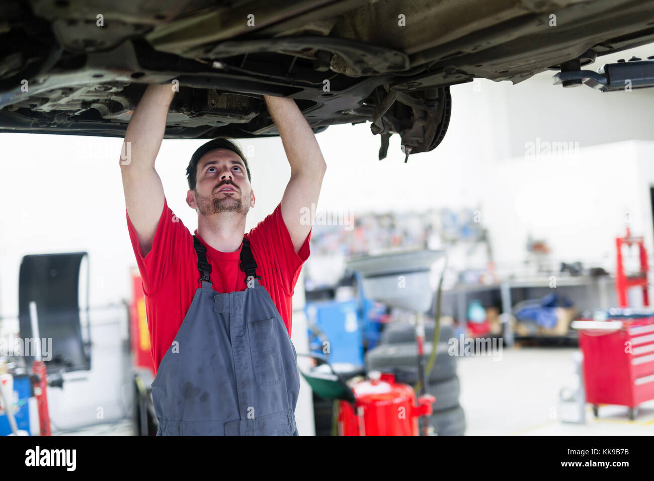 Car mechanic working at automotive service center - Stock Image