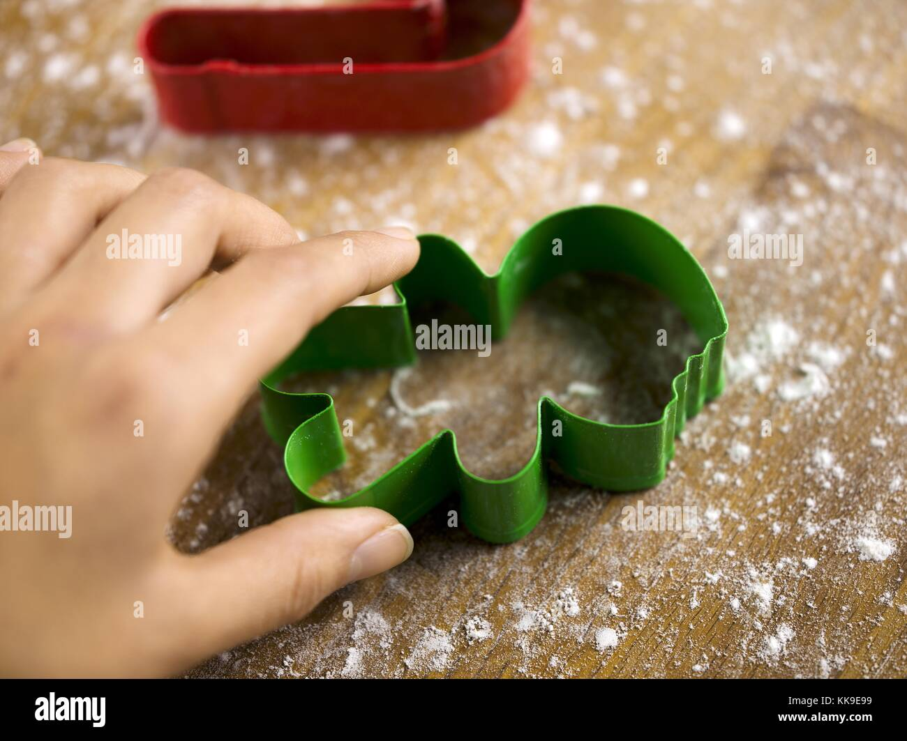 close up shot of a person touching plastic cookie cutter - Stock Image