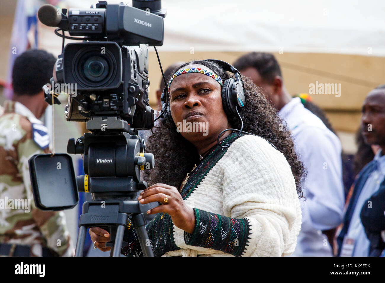 Female camera operator dressed traditionally with braided hair and head band at the Ashenda Festival, Mekele, Ethiopia. Stock Photo