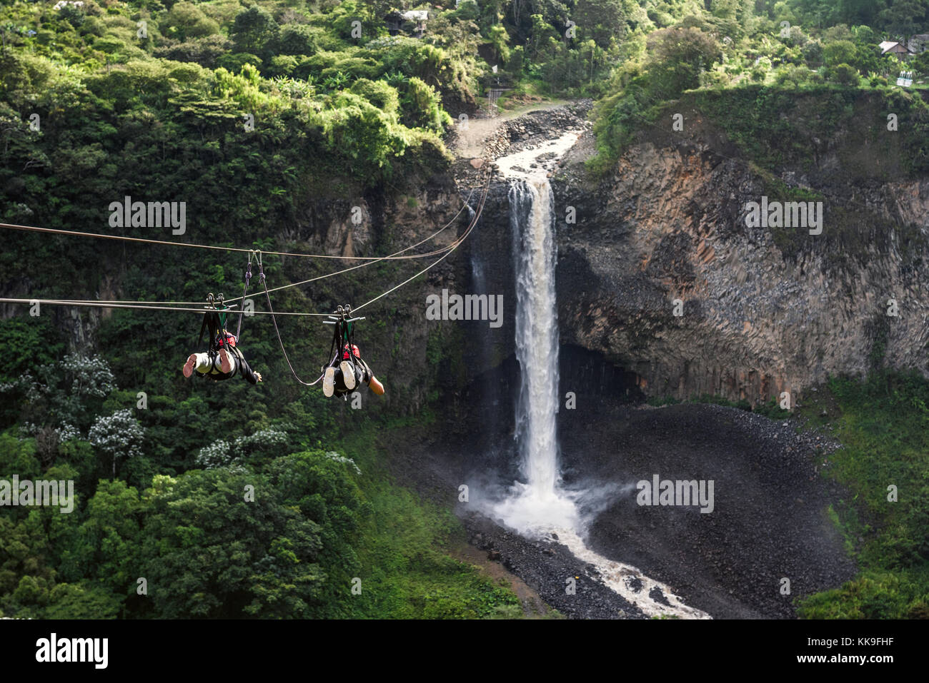 Tourists gliding on the zip line trip against Bridal veil (Manto de la novia), waterfall in Cascades route, Banos, - Stock Image