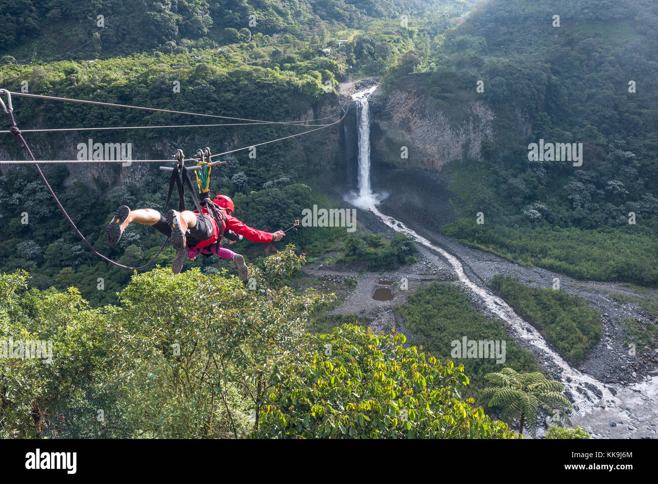 Cascades route, Banos, Ecuador - November 28, 2017: Tourists gliding on the zip line trip against Bridal veil (Manto - Stock Image
