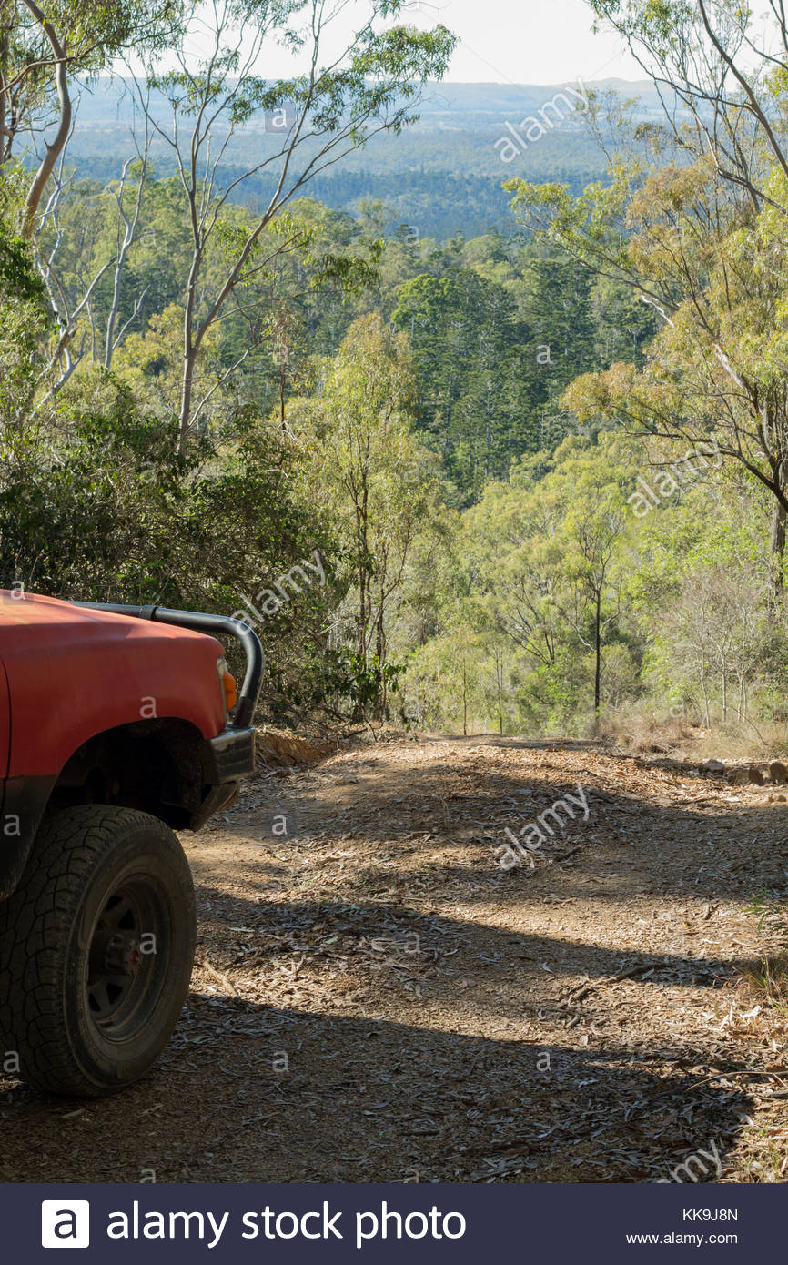 A dirt road leads a four wheel drive down a mountain in Goodnight Scrub National Park in Queensland, Australia. - Stock Image