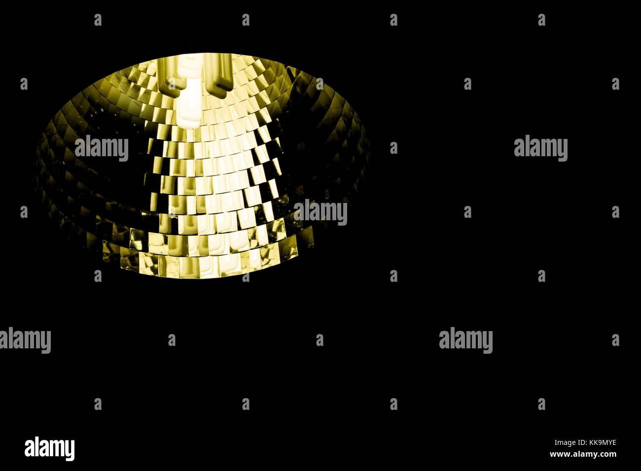A single fluorescent light bulb spot light in a bronze yellow reflector - Stock Image