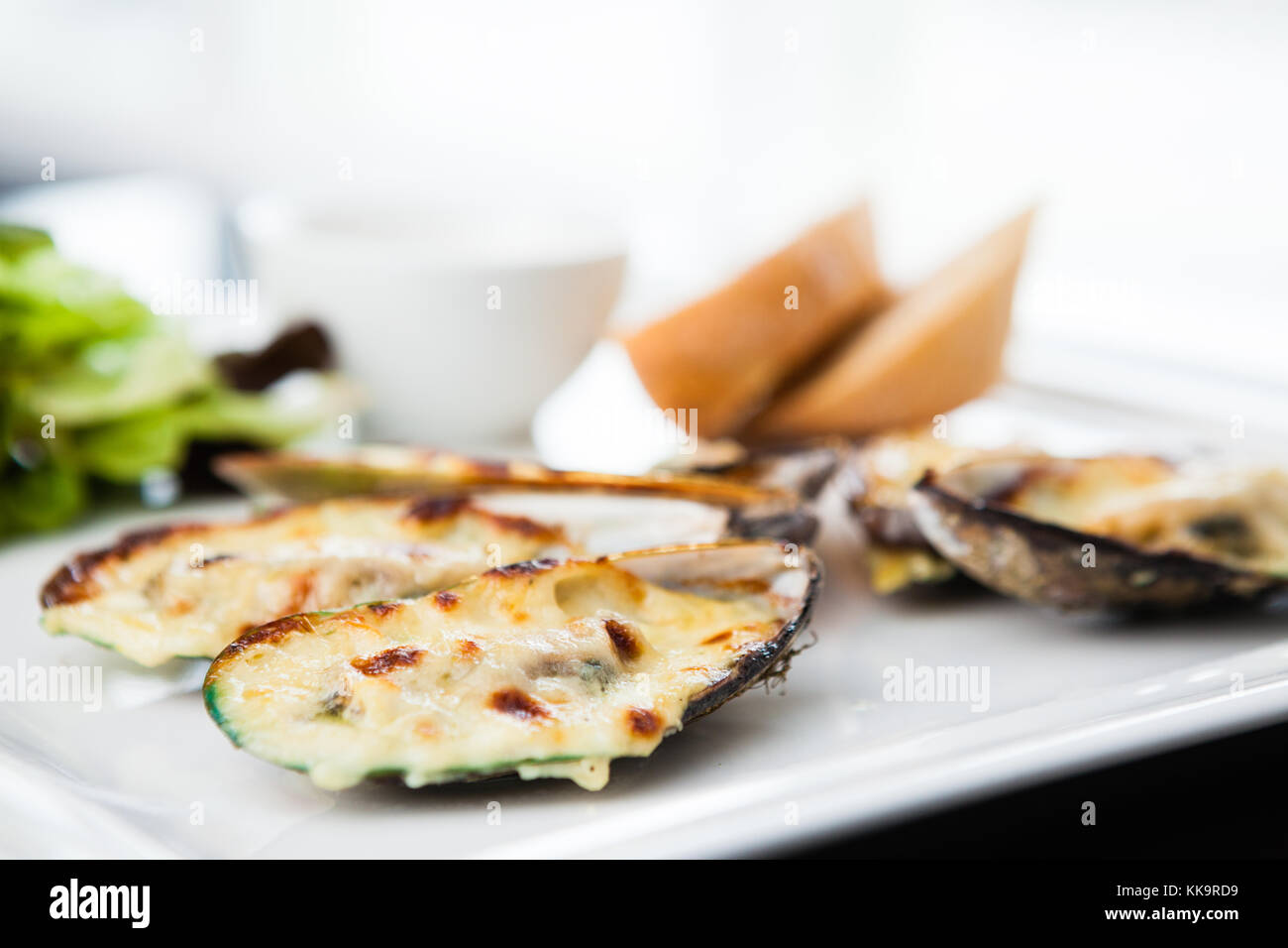 Baked mussels au gratin with salad and sauce - Stock Image