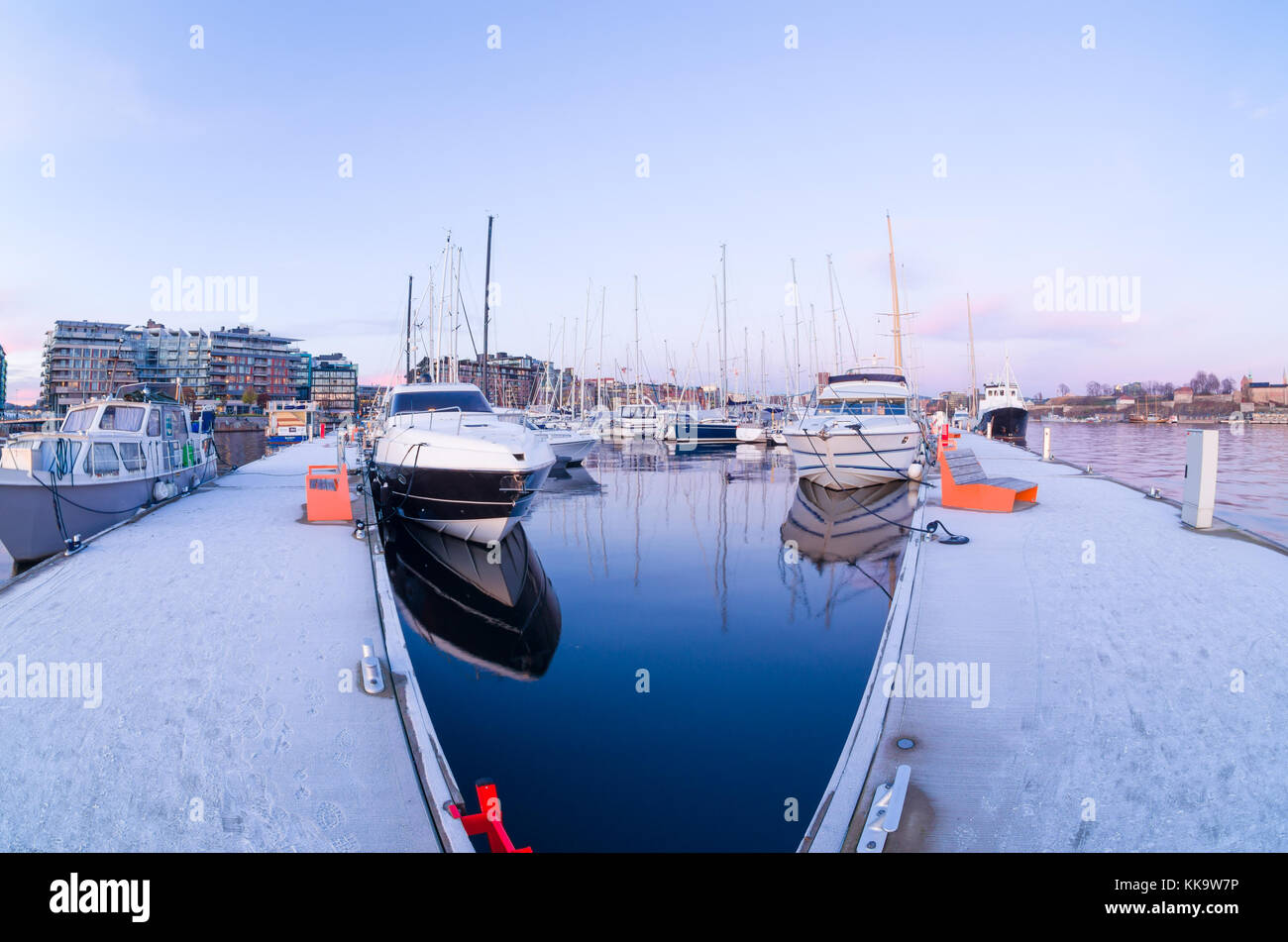Mirror water inside frosty piers of Aker Brygge Marina in Oslo, Norway, at the beginning of the winter. - Stock Image