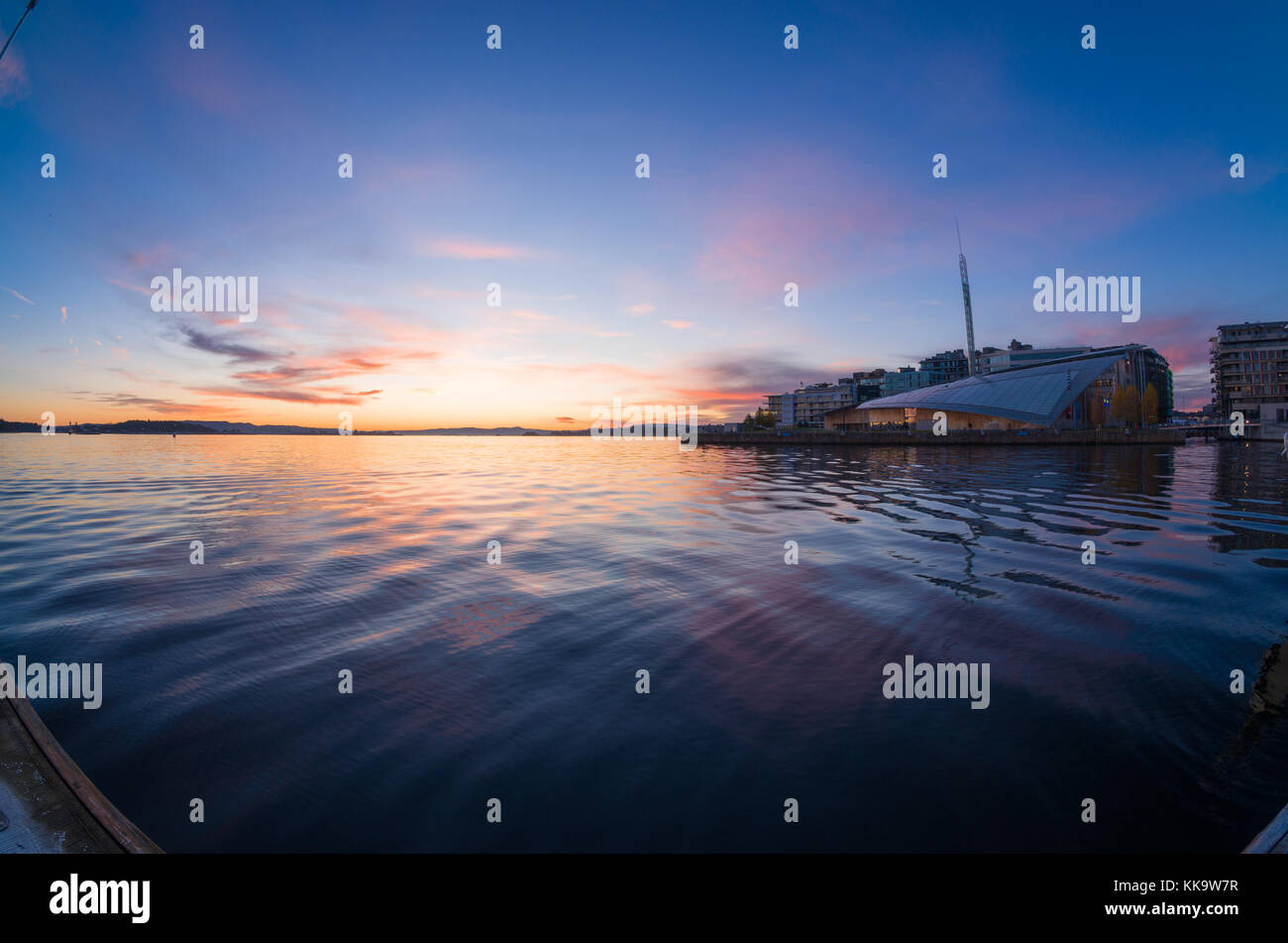 Waterfront of Tjuvholmen, Oslo, Norway, with Astrup Fearnley Museum, under colorful sunset, viewed from floating - Stock Image