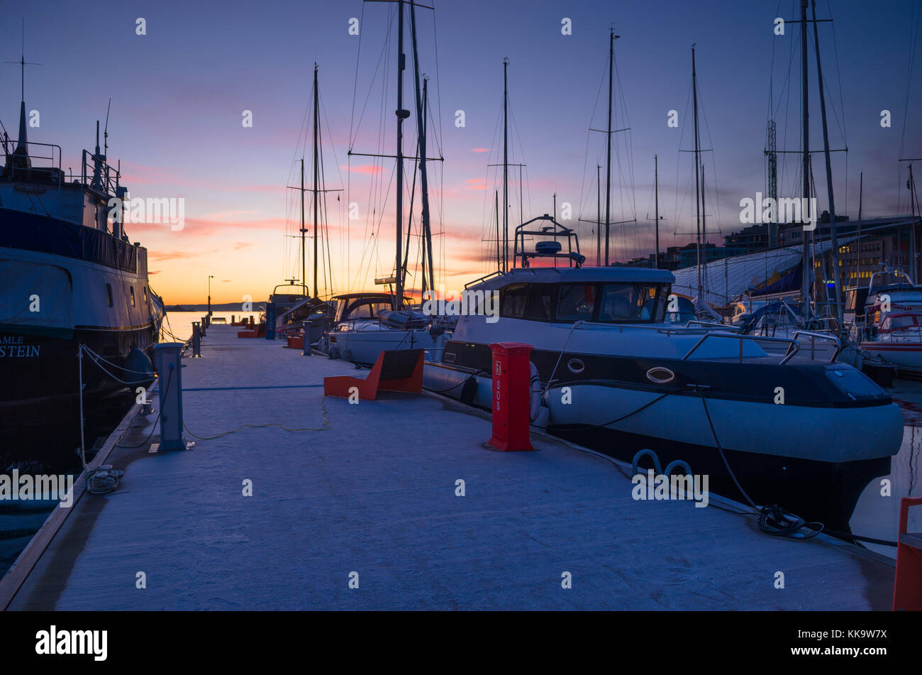 Yachts moored to frosty floating pier in Aker Brygge Marina in Oslo, Norway, with beautiful sunset in the background. - Stock Image