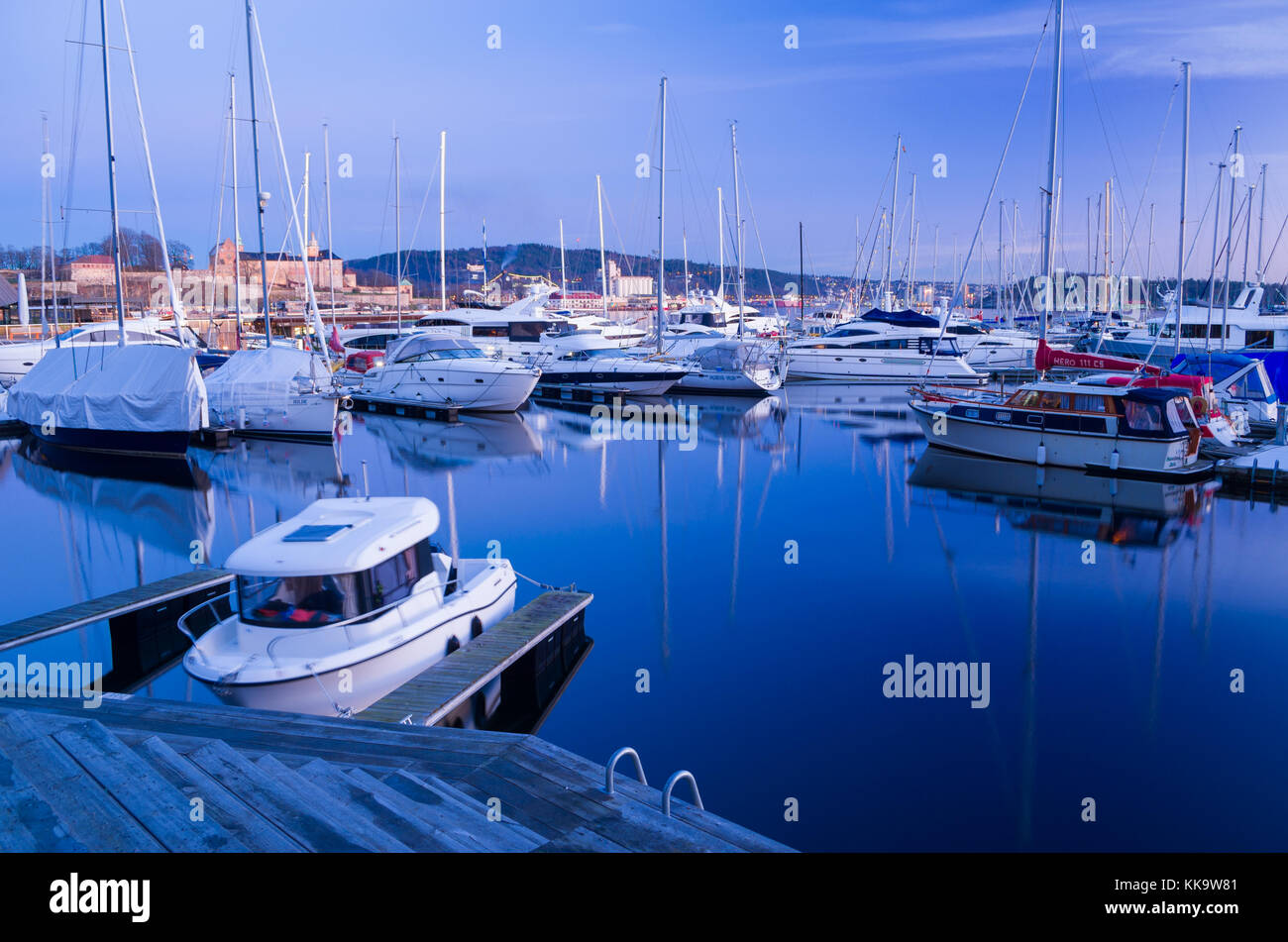 Winter hibernation in Aker Brygge Marina, Oslo, Norway. Sealed yachts are mooring to floating piers, with Akershus - Stock Image
