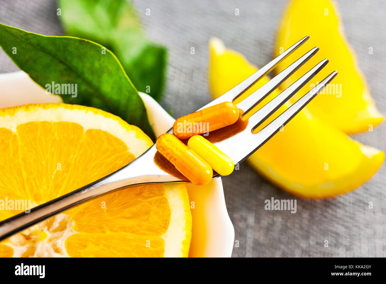 health care - fresh orange fruit and vitamin C - nutition tablets on the fork Stock Photo