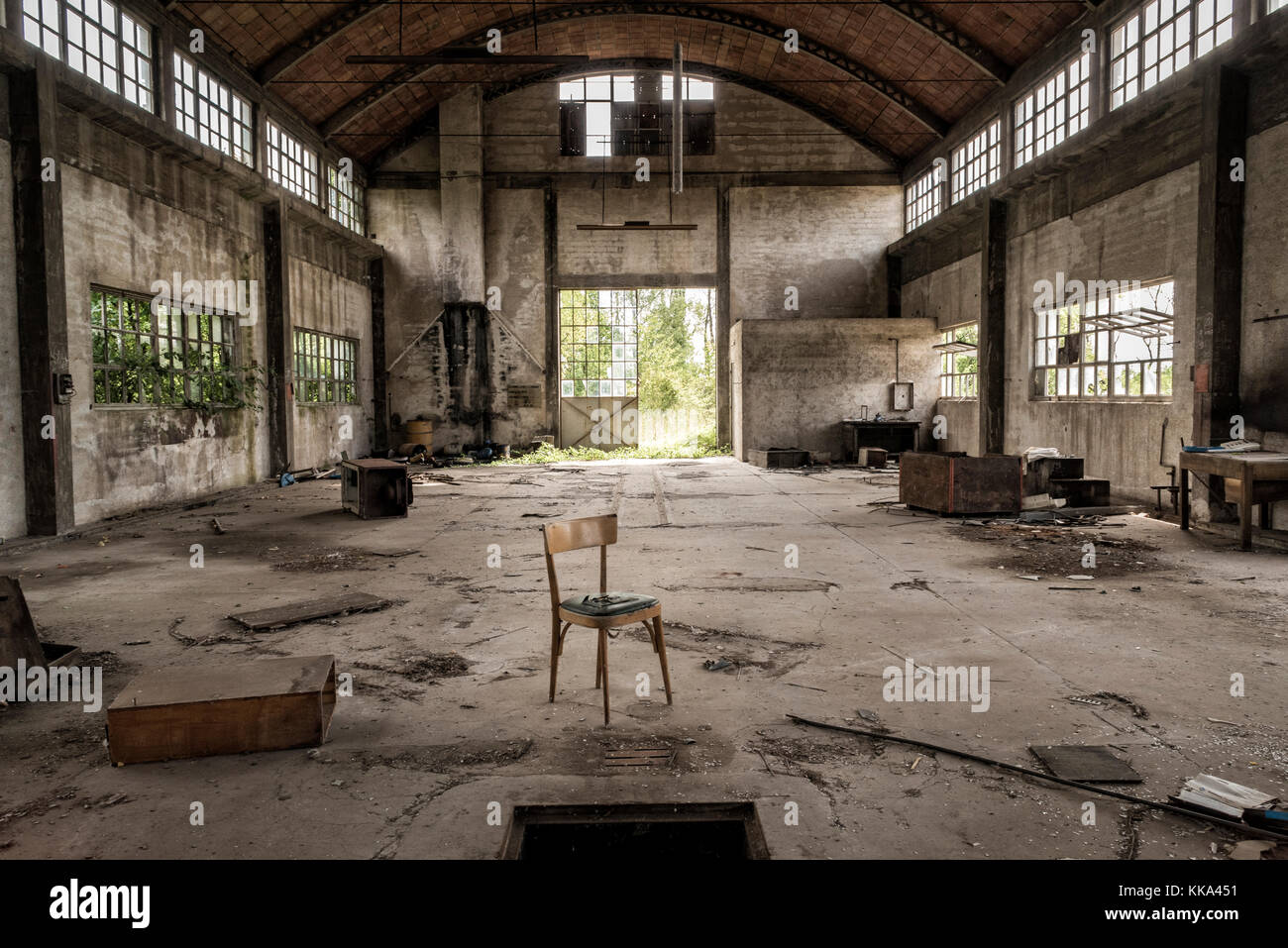 Abandoned factory (central perspective) with chair in foreground - Stock Image
