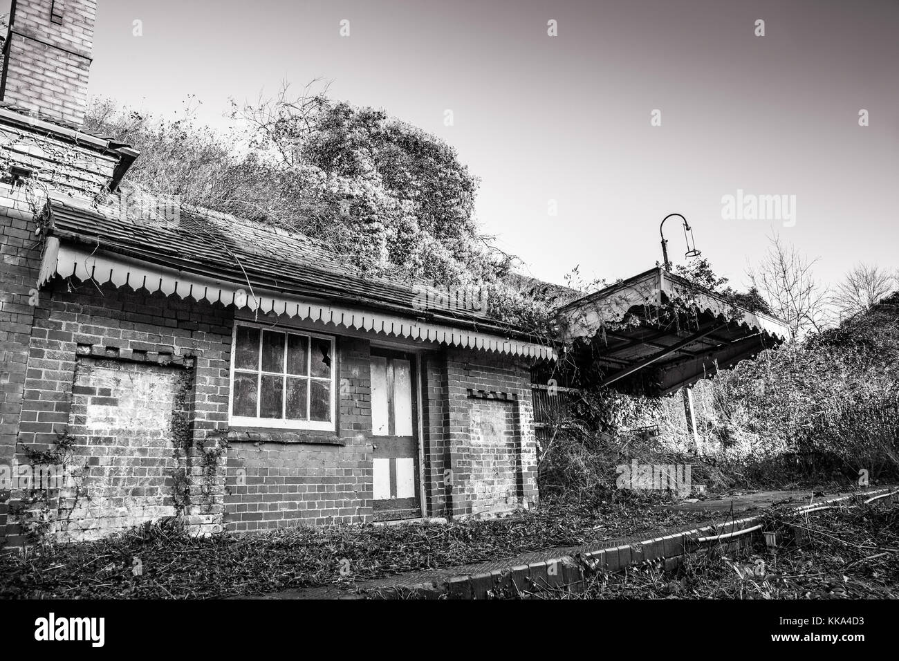 Black & white shot of disused Victorian station house in dilapidated state, in need of significant repair. Bricked - Stock Image