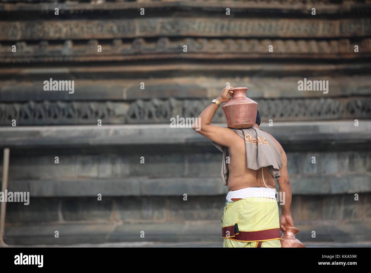 Morning in Chenna Keshava Vishnu Temple - priest with lota kalash pot making offerings - Priester mit Kuferkrug Stock Photo