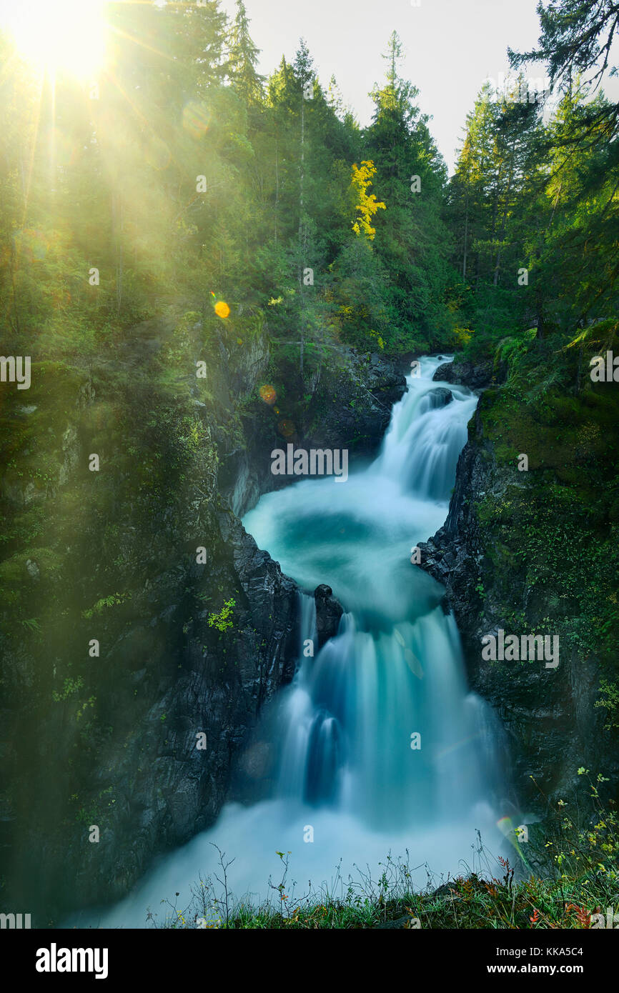 Bright glowing sunshine over beautiful cascade waterfall nature scenery at Little Qualicum Falls Provincial Park, Stock Photo