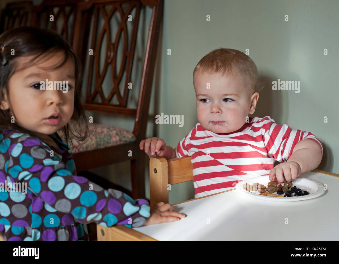 A young boy gives his friend a look when he thinks she may take his food. - Stock Image
