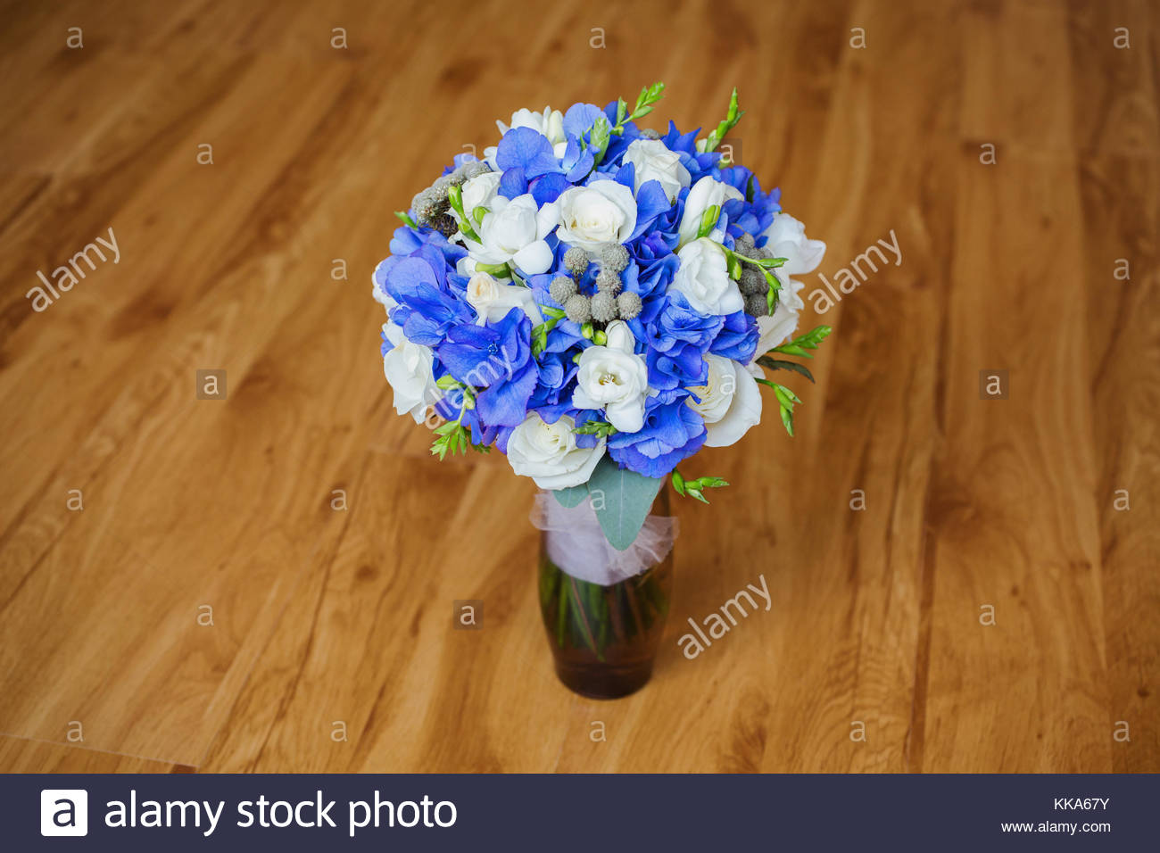 Wedding bouquet of white and blue flowers in a transparent vase wedding bouquet of white and blue flowers in a transparent vase stands on a light background white rose morning bride izmirmasajfo
