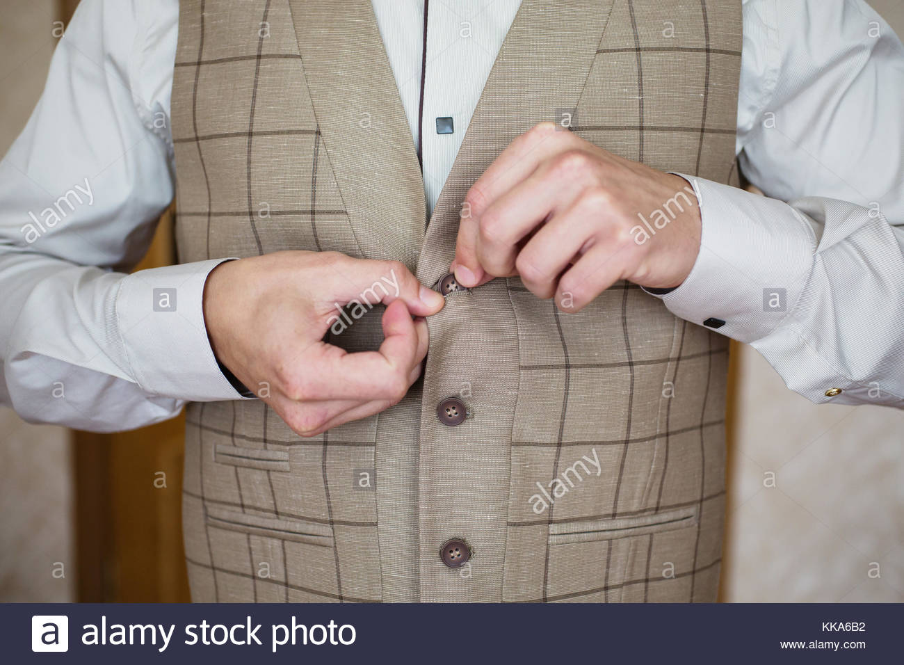 Man buttoning his waistcoat on. Men's style. Professions. Preparing to work on an appointment. - Stock Image