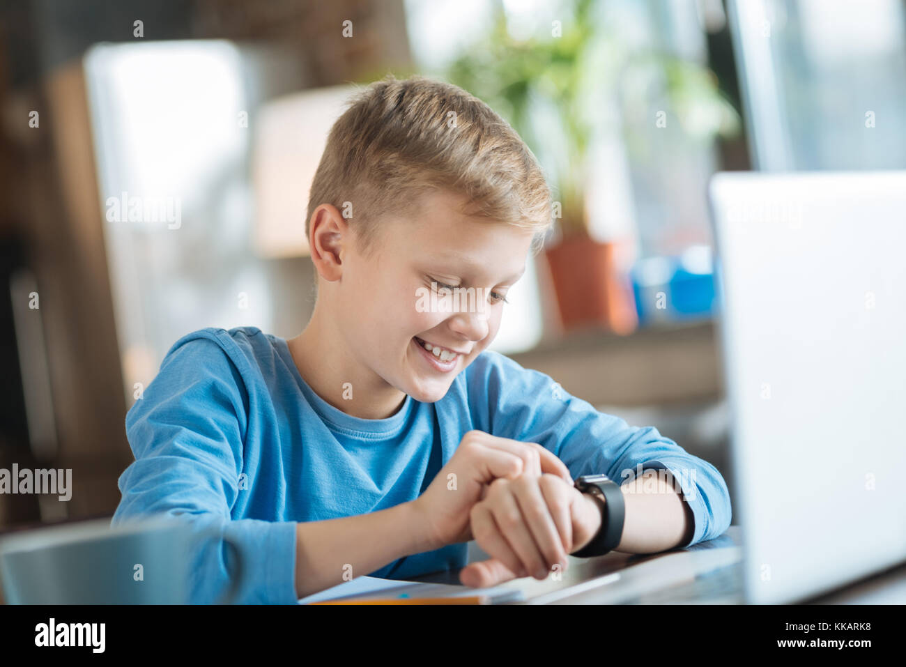 Happy nice boy checking the time - Stock Image