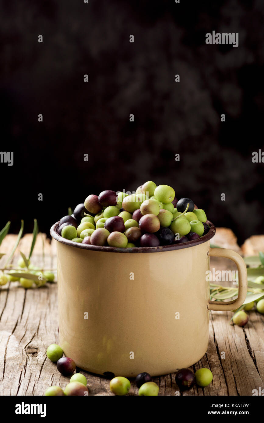 closeup of a handled enamelware pot full of arbequina olives from Catalonia, Spain, on a wooden rustic table, against - Stock Image