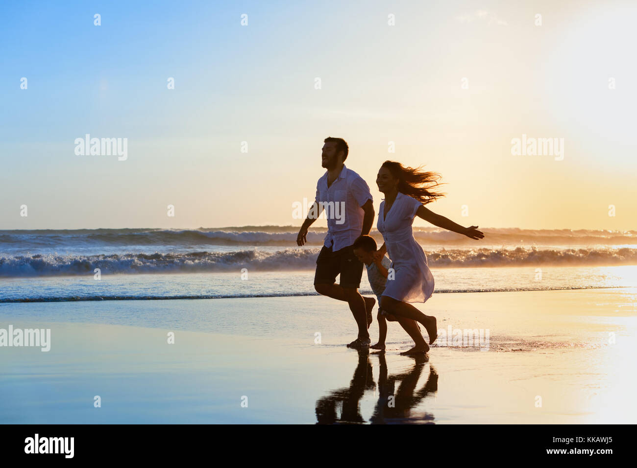 Happy full family - father, mother, baby son have fun together, child run by water pool along sunset sea surf on - Stock Image