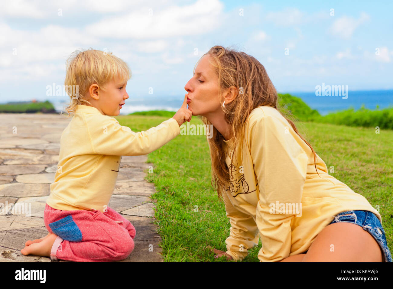 Happy family on outside walk. Child sitting on green grass lawn have fun. Young attractive mother kiss son finger. - Stock Image